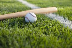 baseball bat and ball on grass near field stripe - stock photo