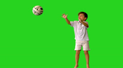 Happy little boy jumping and dropping rugby ball on green screen Stock Footage