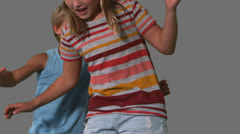 Stock Video Footage of Siblings jumping up and down on grey background