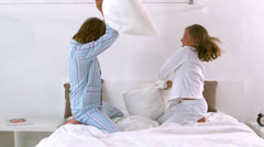 Siblings having a pillow fight on the bed Stock Footage