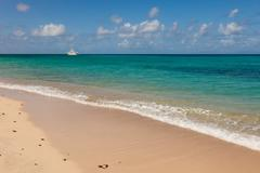 Stock Photo of tropical caribbean beach seascape with motor yacht sailing into distance