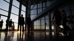 Business people walking through a modern office building at sunset Stock Footage