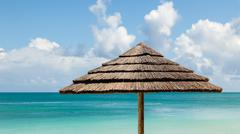 sunny tropical seascape of beach umbrella by sea and sky with clouds - stock photo
