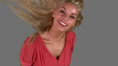 Attractive blonde tossing her hair on grey background - stock footage