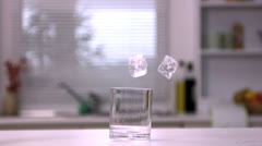 Two ice cubes falling in an empty glass Stock Footage