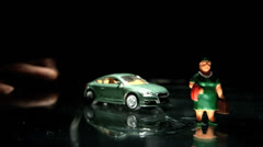 Green toy car hitting a woman figurine Stock Footage