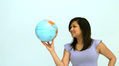 Smiling woman spinning globe on finger Stock Footage