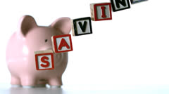 Blocks spelling savings dropping down in front of a pink piggy bank - stock footage