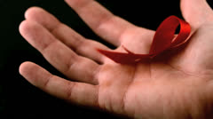 Aids red ribbon symbol falling over a man hand Stock Footage