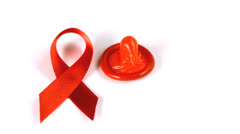 Stock Video Footage of Condom falling over beside red ribbon