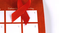 Red ribbon symbol for Aids falling on a calendar - stock footage