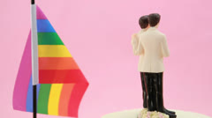 Gay groom cake toppers in front of rainbow flag revolving Stock Footage