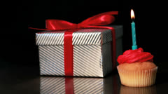 Candle on cupcake blown beside gift Stock Footage