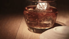 Cigar being placed beside tumbler of whiskey on the rocks Stock Footage