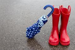 Red rain boots and umbrella Stock Photos