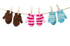 Three mittens hanging on a clothes line Stock Photos