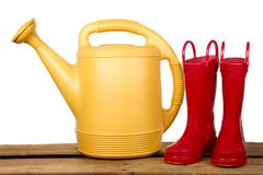 Yellow watering can and red gardening boots Stock Photos