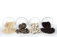 edible seeds spilling out of glass containers - stock photo