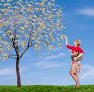 a woman reaching up picking money off a tree - stock photo