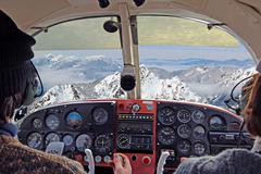 View from over snow covered peaks while flying in small plane Stock Photos