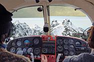 Stock Photo of view from over snow covered peaks while flying in small plane