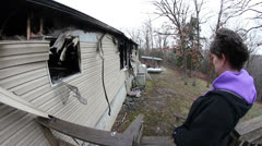 Sad homeowner looking over damage from house fire Stock Footage