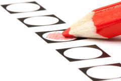 Voting form with red pencil filling in a black circle Stock Photos