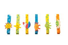 Colorful clothespins with wooden figures lying in a row Stock Photos