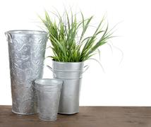 metal gardening containers with grass - stock photo