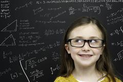 smart young girl stood infront of a blackboard - stock photo