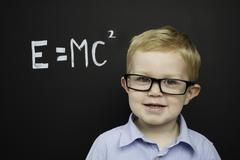 smart young boy stood infront of a blackboard - stock photo
