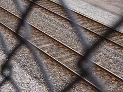 viewing railroad tracks through chain-link fence - stock photo