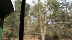 Vehicle shot traditional rail coach rides along mixed forest + pan Stock Footage