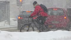 Slow Motion Commuter Cyclist Biker bicycle in heavy Winter snow stormy weather Stock Footage