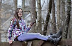 teen aged girl outdoors with cell phone - stock photo