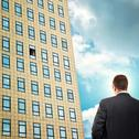 Stock Photo of businessman in front of company building.