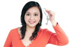 Stock Photo of attractive young woman holding a key