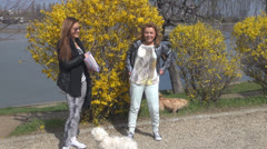 Girls talk, laugh eating popcorn.With dogs in the park Stock Footage
