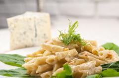 italian pasta penne gorgonzola and pine nuts - stock photo