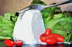 Fresh ricotta cheese cut with fork - stock photo