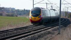 Pendolino tilting passenger train on a curve on the West Coast mainline England - stock footage