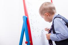 suit up small young boy working on the chalkboard - stock photo