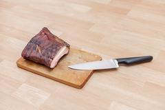 homemade smoked meat on wooden cutting board with big knife - stock photo