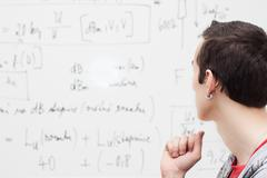 Thinking boy with whiteboard solving equation Stock Photos