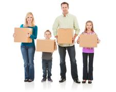family: family all carrying moving boxes - stock photo