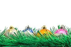 four beautiful christmas decoration balls and green tinsel - stock photo