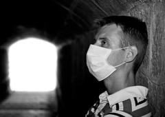 male with gauze bandage in dark tunnel - stock photo