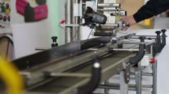 Worker puts bottles in the machine to label them Stock Footage