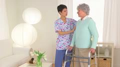 Chinese nurse aiding elderly patient Stock Footage