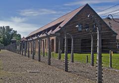 wire fence and barrack in a uschwitz - birkenau concentration camp - stock photo
